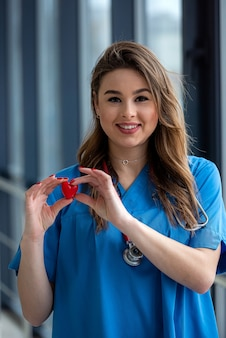 Sorriso bella dottoressa in uniforme blu con stetoscopio che tiene il cuore. assistenza sanitaria