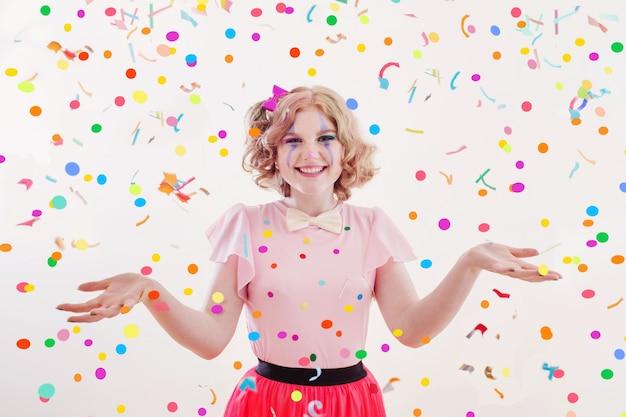 Ragazza dell'adolescente di sorriso in costume del pagliaccio isolato su bianco