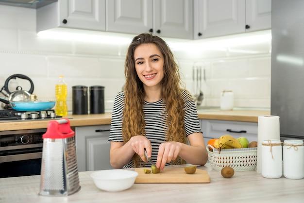 Sorriso giovane donna che cucina insalata fresca con frutta in cucina. uno stile di vita sano. dieta