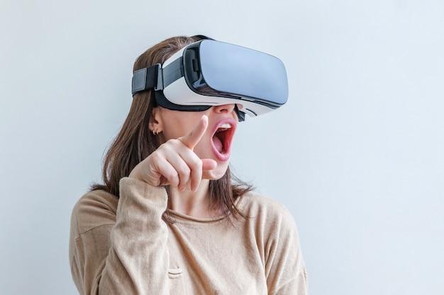 Sorrida la giovane donna che indossa usando la cuffia avricolare del casco di vetro di realtà virtuale vr su fondo bianco. smartphone che utilizza con occhiali per realtà virtuale. tecnologia, simulazione, alta tecnologia, concetto di videogioco.
