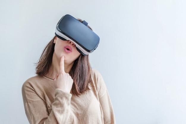Sorridi la giovane donna che indossa usando la cuffia avricolare del casco di vetro di realtà virtuale vr sulla parete bianca. telefono utilizzando con occhiali per realtà virtuale. tecnologia, simulazione, alta tecnologia, concetto di videogioco.