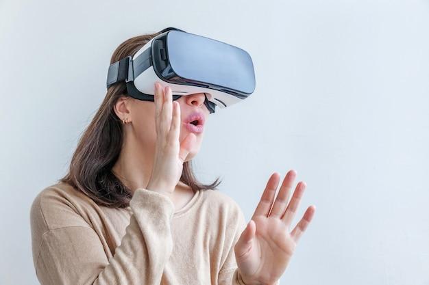 Sorridi la giovane donna che indossa usando la cuffia avricolare del casco di vetro di realtà virtuale vr sulla parete bianca. smartphone che utilizza con occhiali per realtà virtuale. tecnologia, simulazione, alta tecnologia, concetto di videogioco.