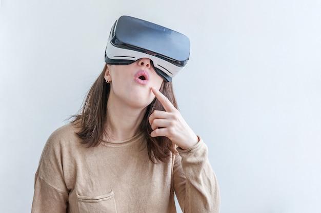 Sorriso giovane donna che indossa utilizzando la realtà virtuale vr occhiali casco auricolare su bianco