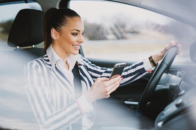 Amico mandante un sms sorridente della donna sveglia mentre guidando attraverso la città.