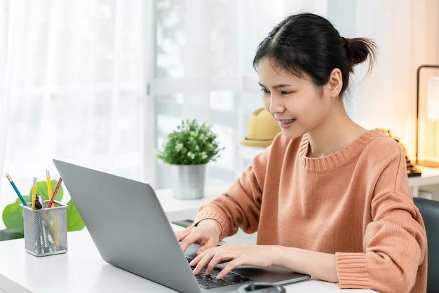 Giovane donna asiatica di smiley che utilizza un computer portatile al tavolo