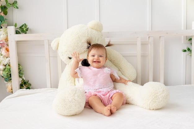 Neonata di smiley che si siede sul letto con l'orsacchiotto