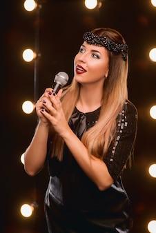 Faccina bella donna con microfono che canta una canzone sul palco del karaoke