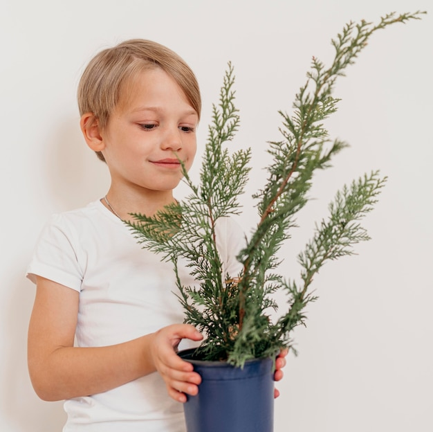 Ragazzo di smiley che tiene il vaso della pianta