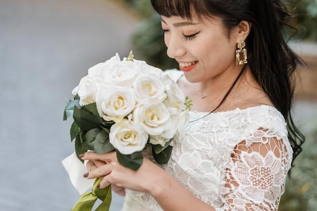 Sposa di smiley che tiene il mazzo di fiori all'aperto