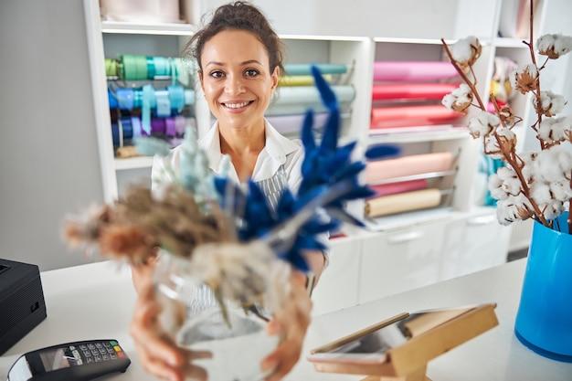 Donna bruna sorridente che lavora in un negozio di fiori