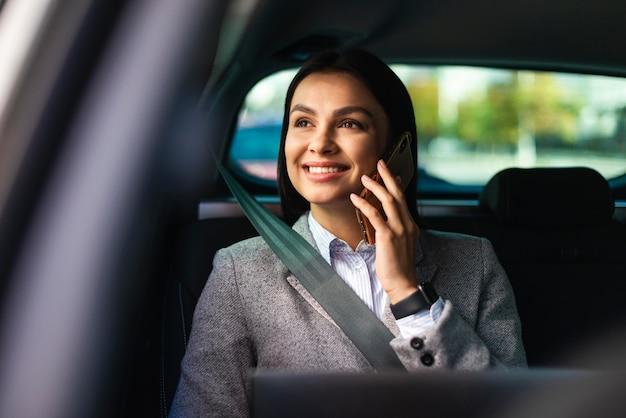 Smiley imprenditrice in macchina parlando al telefono