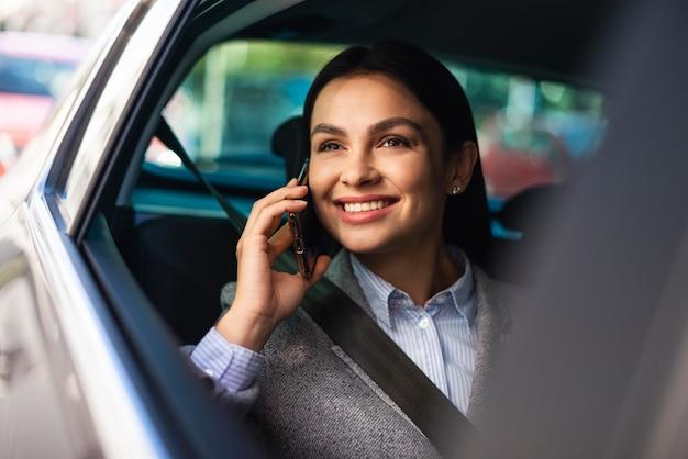 Smiley imprenditrice parlando al telefono mentre si è in macchina