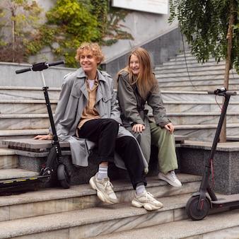 Coppia sorridente seduto accanto a scooter elettrici all'aperto