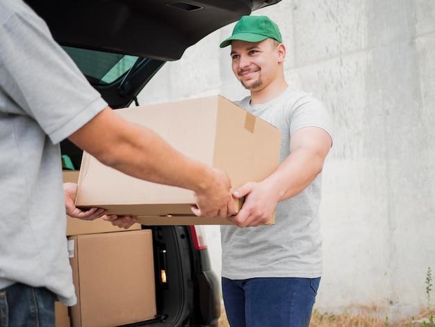 Uomo di consegna di smiley che indossa cappello verde