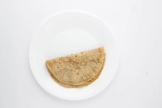 Faccina sorridente prodotto alimentare chapati cibo sano fatto di farina di grano disposto su piatto in ceramica bianca