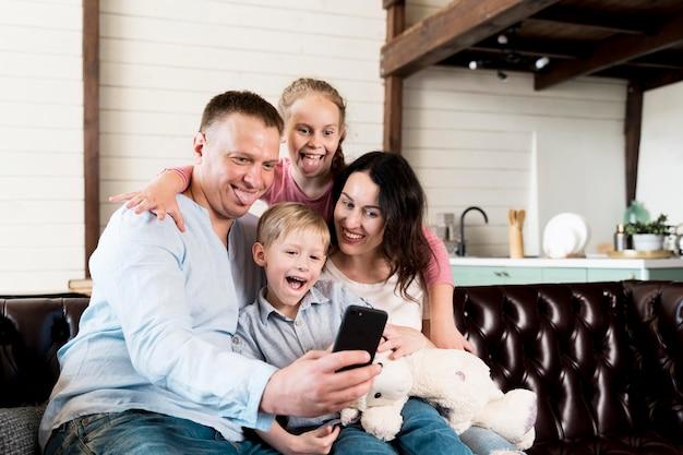 Famiglia di smiley che prende insieme selfie