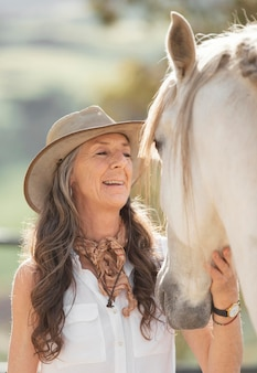 Coltivatore femminile di smiley con il suo cavallo al ranch