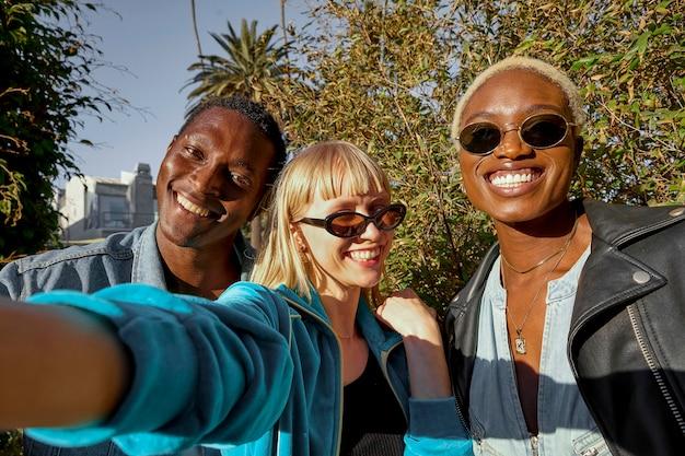 Amici di smiley che prendono il colpo medio del selfie