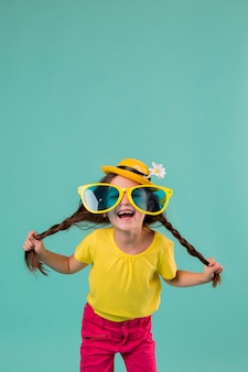 Ragazza di smiley con grandi occhiali da sole e copia spazio