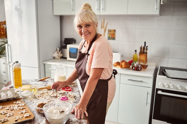 Donna sorridente dai capelli grigi che si prepara a cuocere i biscotti