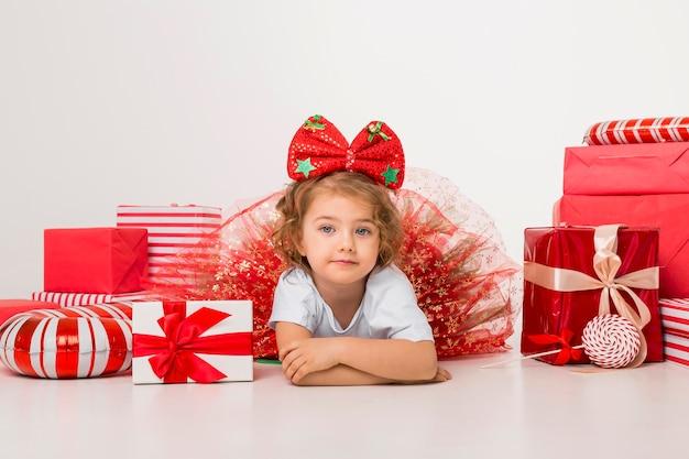 Piccolo bambino sorridente circondato da elementi di natale Foto Premium
