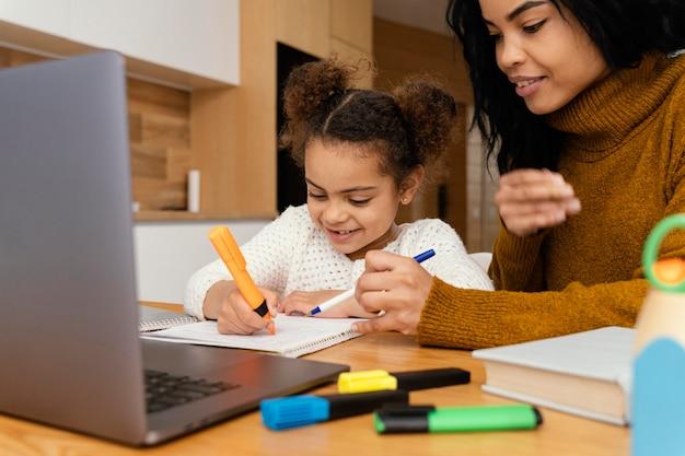 Bambina sorridente e sorella maggiore a casa durante la scuola online