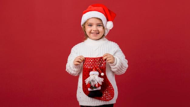 Bambina di smiley che tiene un calzino di natale