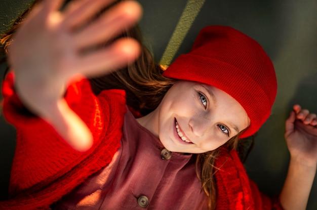Bambina sorridente sdraiato su un campo da basket con il palmo verso l'alto
