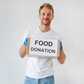 Volontario maschio di smiley con guanti che tengono casella di donazione