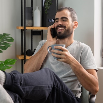 Uomo di smiley che parla al telefono mentre beve il caffè a casa