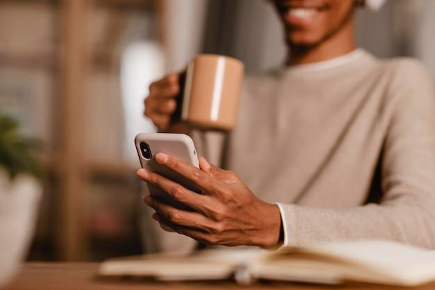 Uomo sorridente utilizzando il suo smartphone e le cuffie mentre beve il caffè