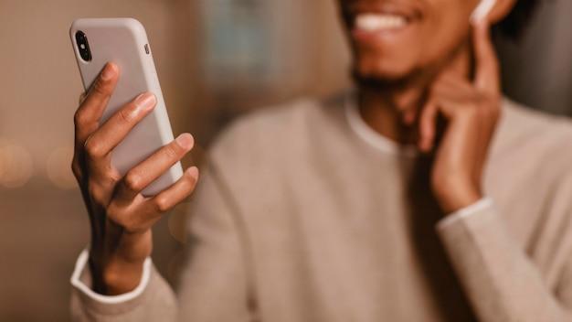 Uomo sorridente che utilizza il suo smartphone a casa con gli auricolari