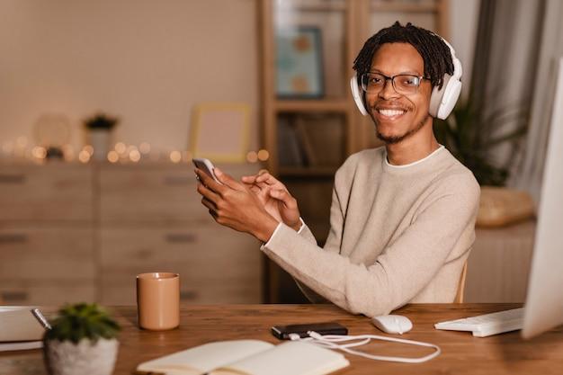 Uomo sorridente che utilizza il suo smartphone mentre è a casa con le cuffie