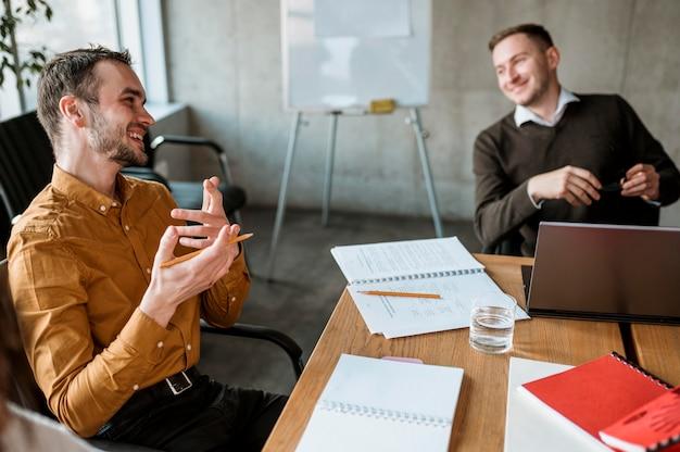 Uomini di smiley che hanno una riunione in ufficio