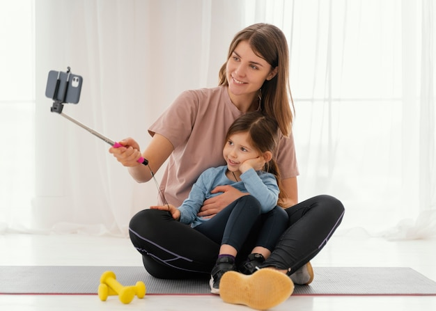 Madre e ragazza di smiley che prendono il colpo pieno del selfie