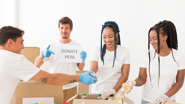 Persone di smiley che si offrono volontariamente per donazioni per i poveri