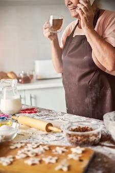 Donna anziana sorridente che fa una telefonata e sorseggia il tè