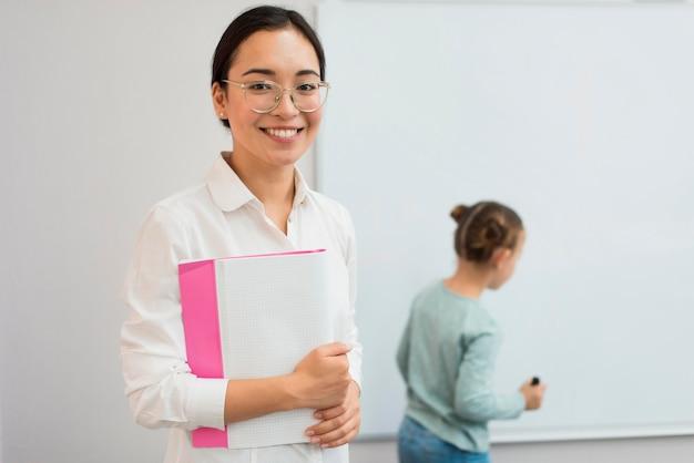 Insegnante di smiley in posa accanto allo studente