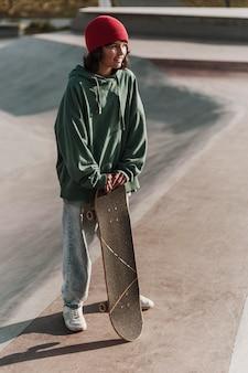 Adolescente sorridente con lo skateboard fuori allo skatepark