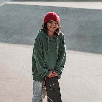 Adolescente sorridente con lo skateboard allo skatepark