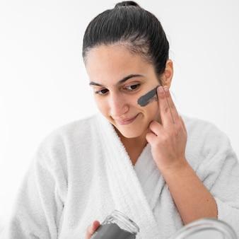 Donna sorridente che applica maschera facciale all'argilla