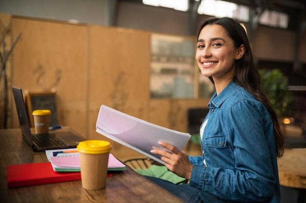 Donna sorridente al caffè in attesa dell'arrivo della sua amica