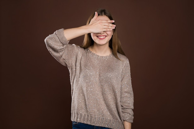 Donna sorridente che copre gli occhi con le mani su sfondo marrone