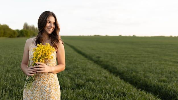 Donna sorridente che tiene i fiori