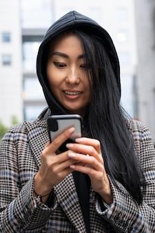 Smiley donna tenendo lo smartphone