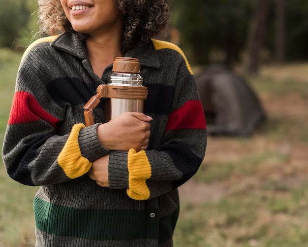 Donna sorridente all'aperto campeggio holding thermos
