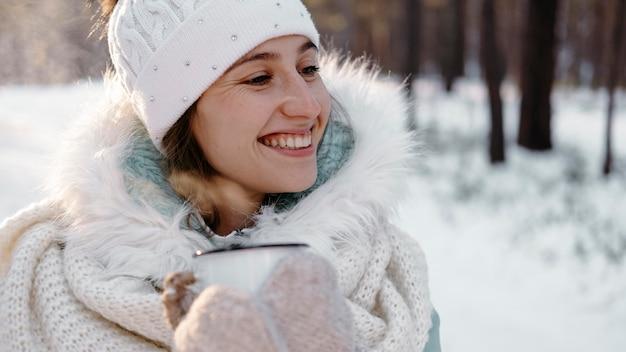 Donna sorridente all'aperto in inverno con una tazza di tè