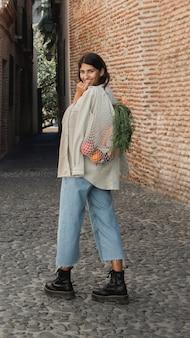 Donna sorridente all'aperto con i sacchetti della spesa