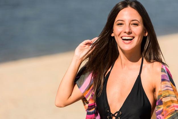 Donna di smiley che posa sulla spiaggia con lo spazio della copia