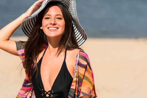 Donna sorridente in posa sulla spiaggia con il cappello